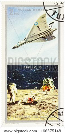 MOSCOW RUSSIA - January 25 2017: A stamp printed in Fujeira shows spacecraft Apollo 12 on the Moon and Vulcan bomber series
