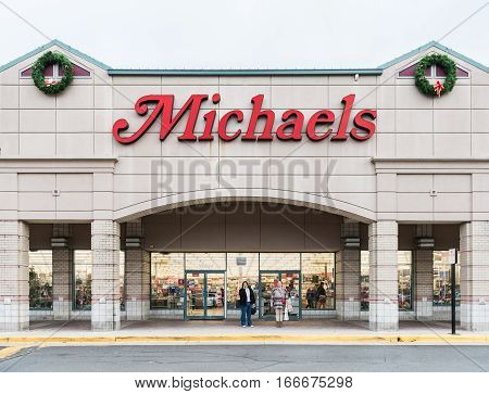 Reston, USA - December 31, 2016: Michaels storefront with red sign and people walking by entrance of store