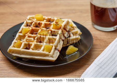 Black plate with homemade waffles, tangerines, chocolate and with cup of coffee and cutlery