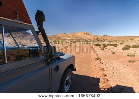 Side of an four by four oldtimer off-road vehicle driving off- road in a desert in Morocco. The vehicle is fully equipped with roof rack  and other off- road items.