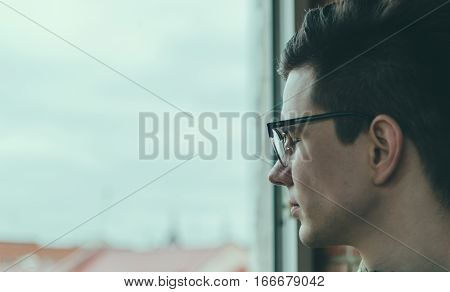 Young man in glasses with closed eyes looking in window