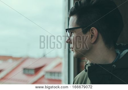 Young man in glasses looking through a window