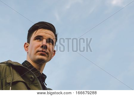 Portrait of the young man on bue sky background