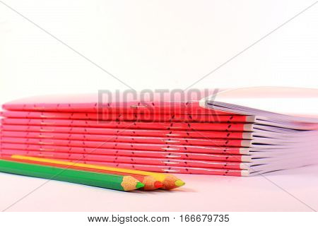Pink notebooks and pencils on a light background