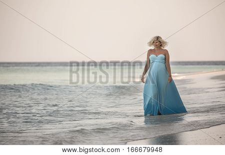 Happy pregnant woman is walking on the Maldivian beach