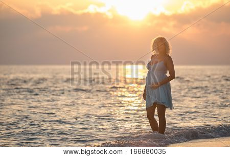 Pregnant beautiful woman is standing on the Maldivian beach during the sunrise