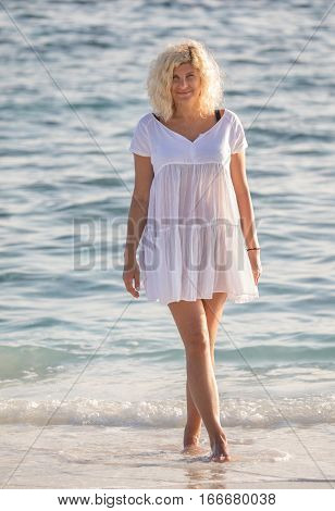 Beautiful woman is standing in water of Indian ocean