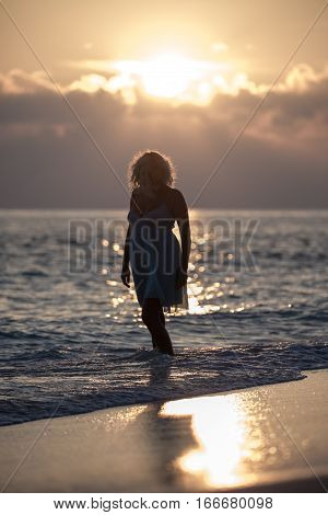 Girl is walking on the Maldivian beach during the sunrise