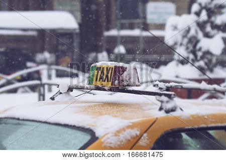 closeup of a yellow taxi roof with the sign covered in snow city scene winter time