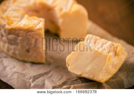 Portion Cut From Whole Golden Camembert Cheese On Paper Sheet