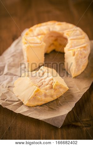Portion Cut From Whole Golden Camembert Cheese On Wooden Board