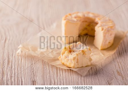 Portions Of Golden Camembert Cheese On White Board