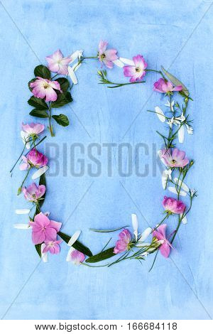 Beautiful Spring frame of flowers on blue background