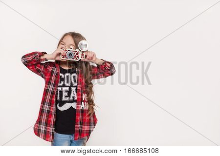 Girl taking a picture with a retro camera isolated on white background. Cute Little kid taking pictures