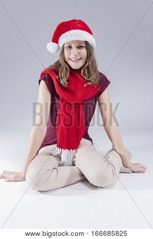 Dental Concepts and Ideas. Happy Caucasian Teenager in Santa Hat With Teeth Brackets. Sitting on Floor Against White. Vertical Image Composition