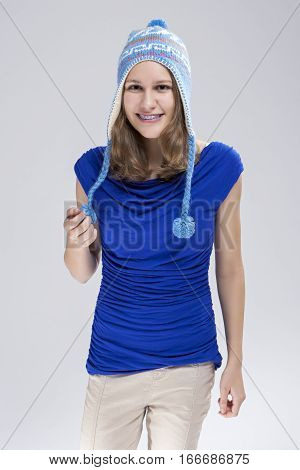 Dental Cure and Treatment. Smiling Caucasian Teenager With Teeth Brackets in Hat Against White Background. Vertical Image