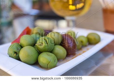 Marinated olives with herbs and spices in a small plate on the tapas bar table a typical Spanish black and green split olive. In the background a blurred beer