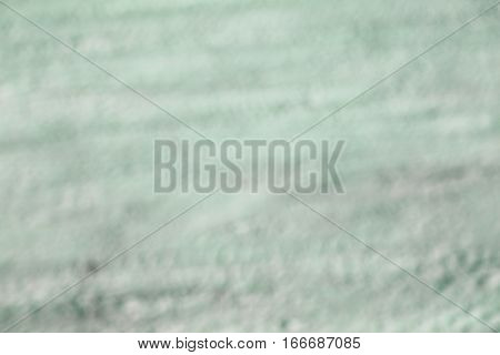Green blurred background consisting of a textured surface