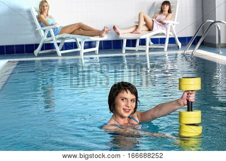 Young beautiful woman doing aqua gym exercise with water dumbbell in pool over relaxing girls background