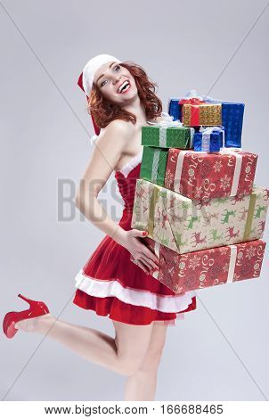 Christmas and New Year Concept and Ideas. Positive Caucasian Snow Maiden Holding a Big Stack of Gift Boxes on Hands and Smiling. Posing on White. Vertical Image
