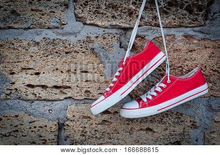 pair of red sneakers sport on the background wall with brickwork empty space
