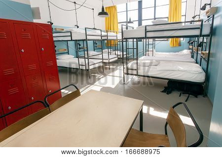 Metal locker table and double-decker beds inside hostel room with tall windows.