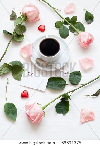 St Valentines day still life - cup of coffee peach roses blank love card and heart shaped candies, St Valentines day love romantic background. St Valentines day still life