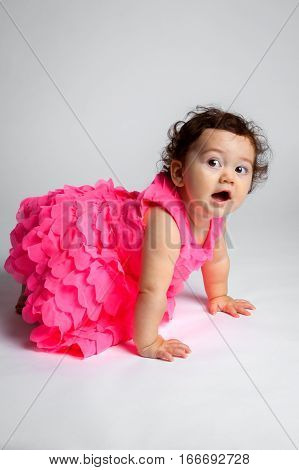 A mischeivious baby looks questioning as she tries to crawl away from the camera. She seems to be sneaking away quietly.