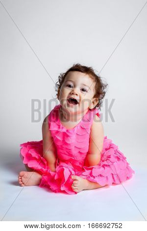 A happy baby in a pink frilly dress leans forward with a big open mouth smile. She is sitting in a portrait studio on a white background.