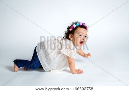 An adorable and excited baby crawls with hand up high against a white studio background. She is proud of herself in achieving her milestones.