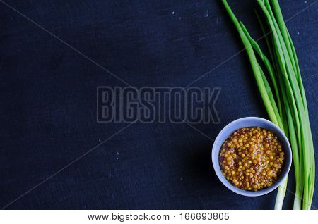 Dijon mustard in a little gravy dish with spring onion on black slate background