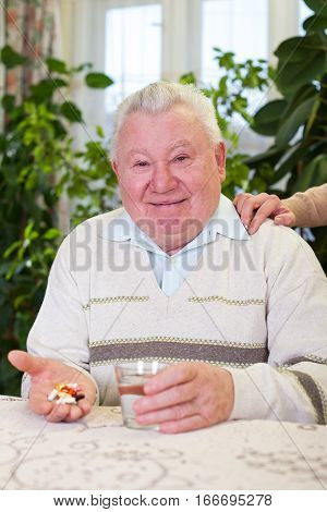 Picture of an elderly man holding his pills and a glass of water