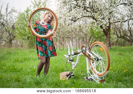 Female Cyclist With Vintage White Bicycle In Spring Garden