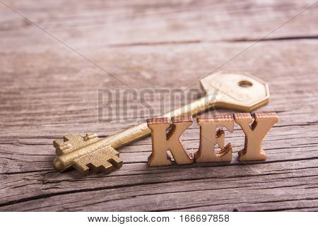 word key made of wooden letters with a golden key on old boards