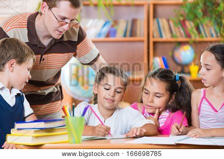 Portrait Of Diligent Schoolkids And Their Teacher