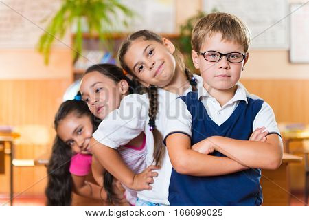 Four Adorable Schoolchildren Standing In Classroom