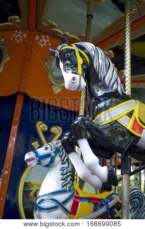 Two colorful carousel horses on funfair in sunny day