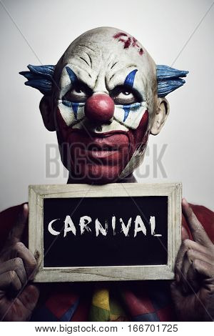portrait of a scary evil clown with a chalkboard with the word carnival written in it