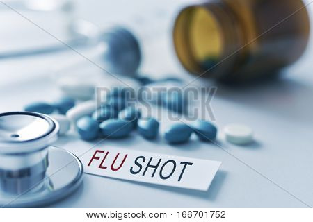 closeup of the desk of a doctors office with a stethoscope a bottle with pills a piece of paper with the text flu shot and a syringe in the background