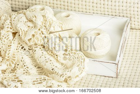crochet tablecloth crochet hooks and balls of cotton thread on a white woolen plaid