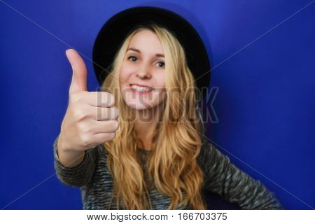 Smiling girl shows his thumbs up. Cheerful busineswoman showing thumb up. mid-level manager. Picture of joyful young woman wearing black hat over blue background. Look at camera. gesture thumbs up.
