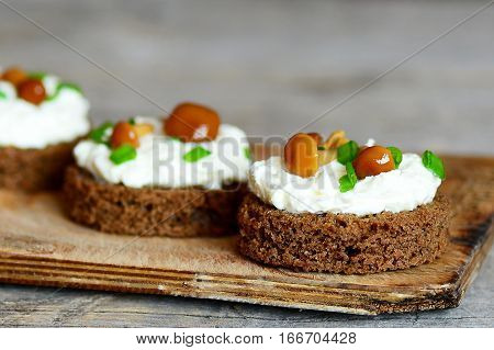 Delicious canape with soft cheese and mushrooms on a board on a wooden background. Canape cooked from brown bread, soft cheese and canned mushrooms. Homemade holiday appetizer. Closeup