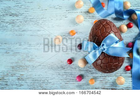 Chocolate Easter egg with color ribbon bow on wooden background