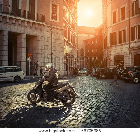 ROME - JANUARY 07: Scooters on the road on the street under sun light at January 07, 2017 in Rome. Scooters are the symbol of Rome - most popular historical travel place of the Italy and the world.