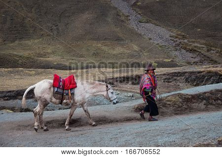 Rainbow Mountains, Peru - October 8, 2016: Native peruvian man wearing traditional clothes and hat with his horse goes uphill.