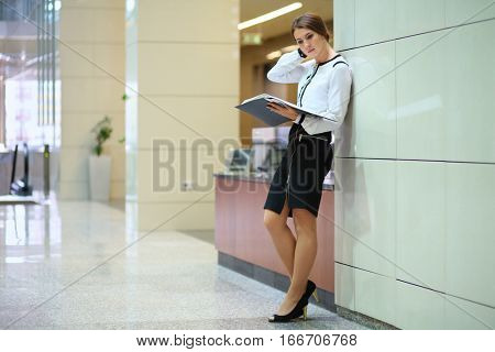The woman with the open folder standing near the wall in the lobby of the business center