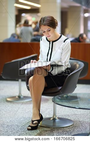 The woman with the open folder sitting on a black chair in the lobby of the business center