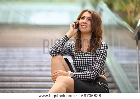 A young woman in a shortened top with long sleeves and black skirt sitting on the marble staircase and talking on mobile