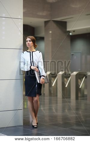 The business woman in a white blouse and a black skirt with the folder standing in the lobby in front of turnstiles in business center