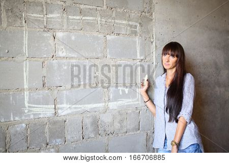 Woman with long hair with piece of chalk standing near the concrete wall with a painted TV on a wall on a construction site